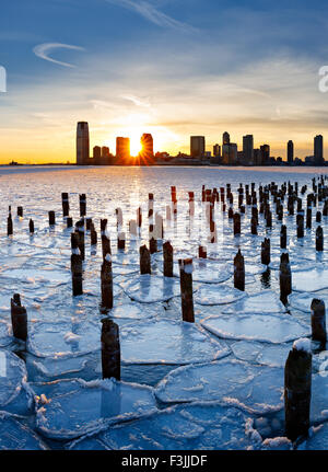 Wood pilings from New York old pier sticking out through the ice on Hudson River at sunset with Jersey City buildings - Stock Photo