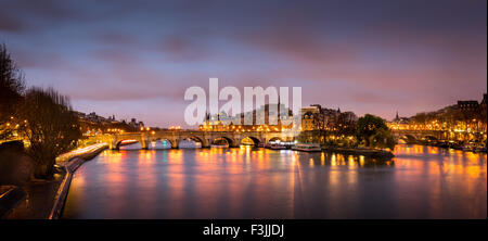 Sunrise in the heart of Paris, France with Ile de la Cite and Pont Neuf. A calm Seine River reflects the city lights. - Stock Photo