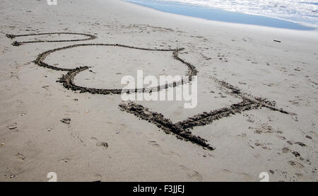I 'heart' u written in the sand on a beach in France. A wave breaks in the top right hand corner.  The heart symbolises - Stock Photo