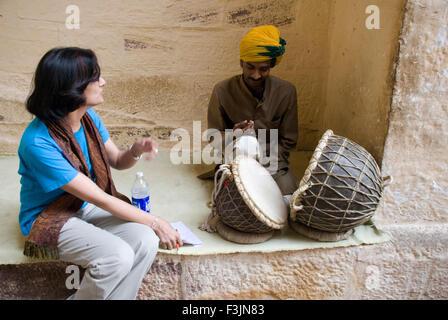 A Young lady watching musician who playing drums at Mehrang Garh fort at Jodhpur ; Rajasthan ; India NO MR - Stock Photo