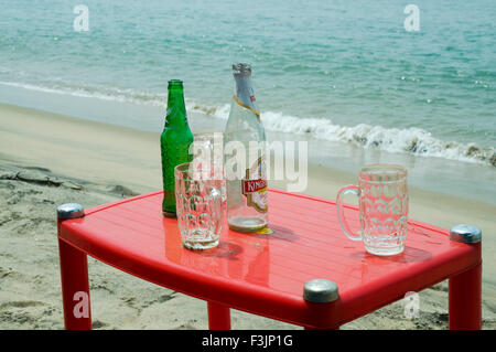 empty beer bottle and mugs on plastic table at Devbaug beach Sindhudurgh ; Maharashtra ; India - Stock Photo
