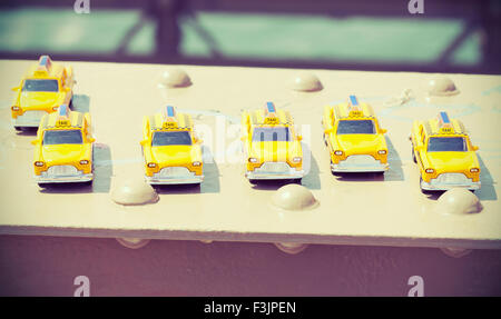 Cross processed instagram photo of taxi toys on Brooklyn Bridge, travel concept. - Stock Photo