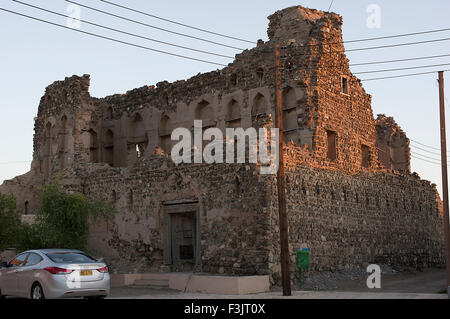 Ornate ancient adobe fortress in ruins in a town in the Sultanate of Oman, a safe, friendly Gulf State holiday destination - Stock Photo