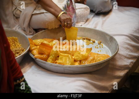 Indian Prasad  or religious offering is packed in yellow pack under big plate tray hold by hand - Stock Photo