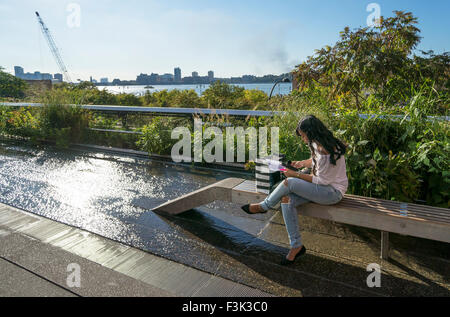 Young woman working, sitting on a wooden bench on the High Line in New York City - Stock Photo