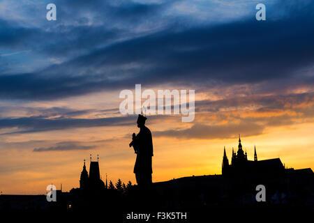 St; John of Nepomuk statue on Charles Bridge; Prague; Czech Republic; with St Vitus's cathadral and Little Quarter - Stock Photo