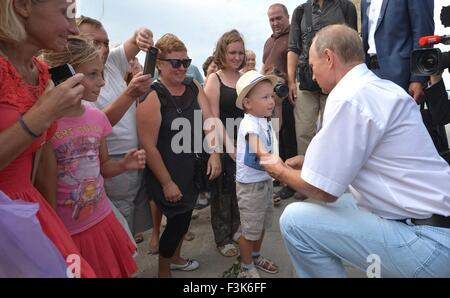 Russian President Vladimir Putin greets a young boy during a tour of the ancient Greek archaeological site of Chersonesus - Stock Photo
