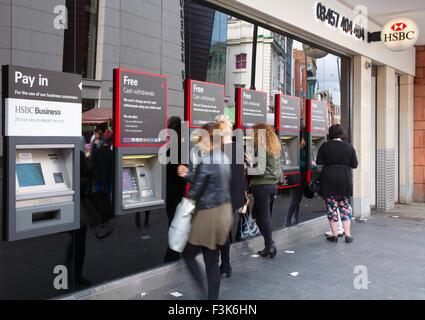 Row of customers, and ATM or hole-in-the-wall machines outside HSBC banks, Liverpool, Merseyside, UK - Stock Photo