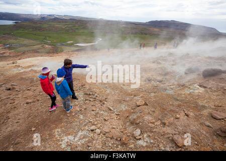 Visitors beside steaming volcanic vents at Seltun, Krysuvik geothermal area, Reykjanes Peninsula, Iceland. - Stock Photo