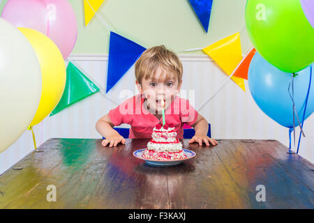 Adorable kid blowing out the candle on his birthday cake - Stock Photo