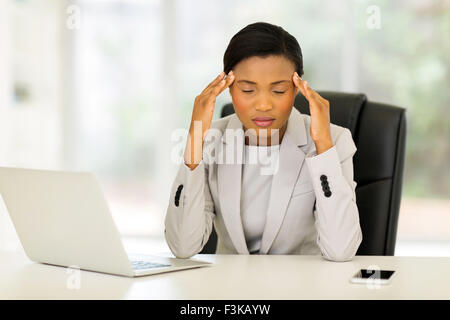 overworked African American businesswoman having headache - Stock Photo