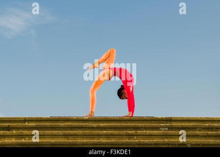 attractive woman practicing yoga urdhva dhanurasana pose