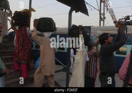 Lahore, Pakistan. 08th Oct, 2015. Passengers of Samjhuata express carry their luggage upon arriving in Lahore railway - Stock Photo