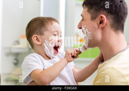 Cute child boy shaving father in bathroom - Stock Photo