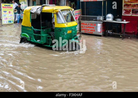 A motor rikshaw is moving through the flooded streets of the suburb Paharganj after a heavy monsoon rainfall - Stock Photo