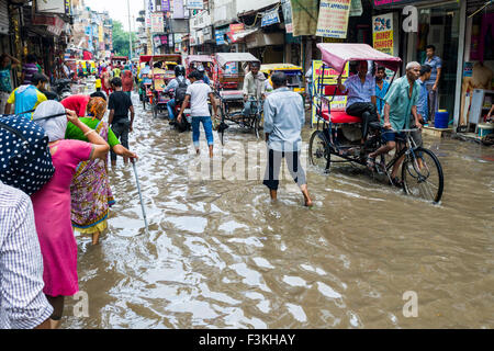 Many people and motor rikshaws are moving through the flooded streets of the suburb Paharganj after a heavy monsoon - Stock Photo