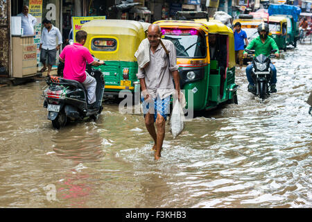 People, motobikes and motor rikshaws are moving through the flooded streets of the suburb Paharganj after a heavy - Stock Photo