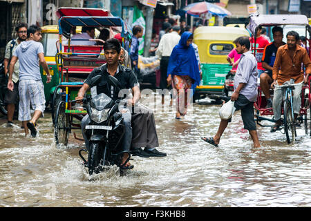 People, motobikes and cycle rikshaws are moving through the flooded streets of the suburb Paharganj after a heavy - Stock Photo