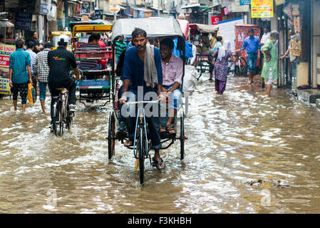 Many people and cycle rikshaws are moving through the flooded streets of the suburb Paharganj after a heavy monsoon - Stock Photo
