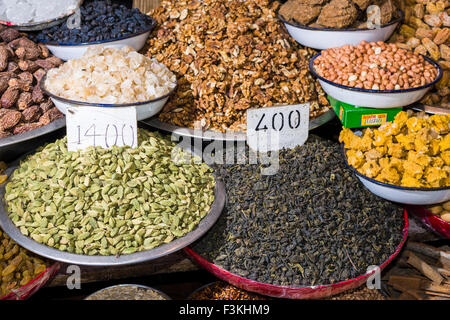 Cardamon, walnuts, peanuts, dates and black tea are displayed in bowls in the Old Delhi spice market - Stock Photo