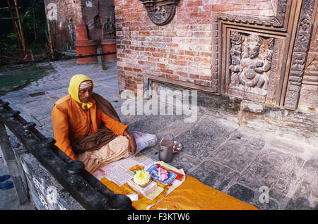 Hindu priest reading holy scriptures in front of a temple ( Nepal) - Stock Photo