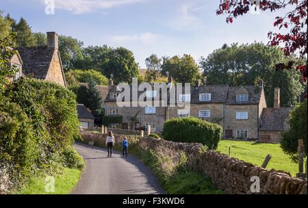 Family dog walking in Cotswold village, England. - Stock Photo