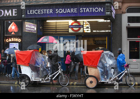 London rickshaw drivers wait outside Leicester Square Underground station for commuters on a wet day, London, England, UK