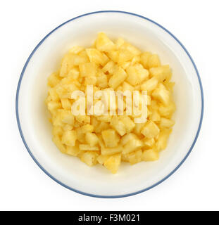 Fresh juicy pineapple pieces in a round white bowl isolated against a white background. - Stock Photo