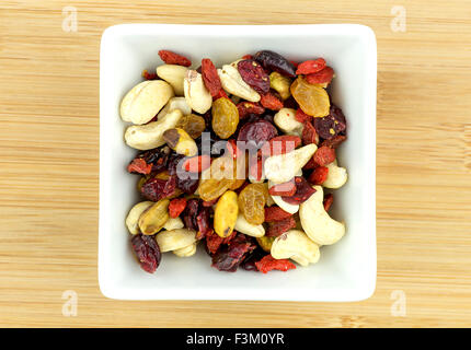 Mixed fruit and nuts in white bowl on wooden background - Stock Photo