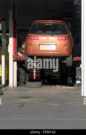 car on ramp in garage for repairs by mechanic service servicing cars repairing repair cost costs running tire tires - Stock Photo