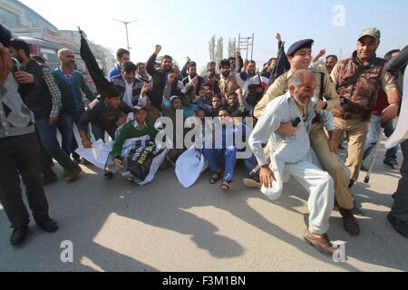 Srinagar, Kashmir. 9th October, 2015. Indian policemen detain a supporter of Engineer Rashid Ahmed, an independent - Stock Photo