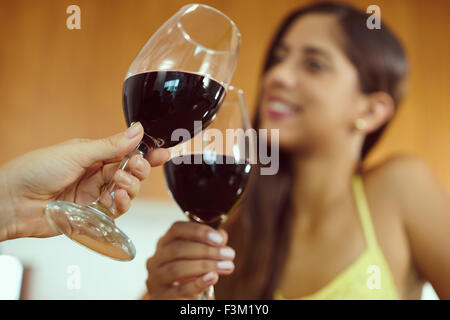 Two female friends at home, relaxing with a glass of red wine. The girls smile and celebrate making a toast. Focus - Stock Photo