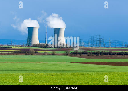 The nuclear powerplant Grafenrheinfeld is steaming out of the cooling towers against dark clouds, located in agricultural - Stock Photo