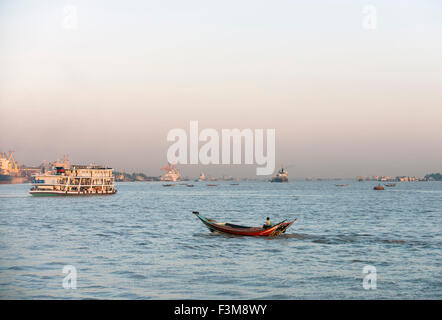 Passenger boat and small fishing-boat on Irrawaddy river, Burma - Stock Photo