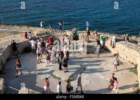 Tourists enjoy the late afternoon light on the coast at Kyrenia harbor in North Cyprus  KATHY DEWITT - Stock Photo