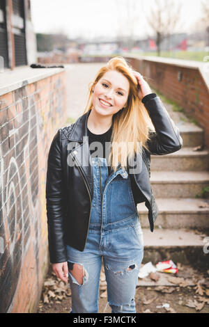 Knee figure of young beautiful blonde straight hair woman in the city, touching her hair, smiling, looking in camera - Stock Photo