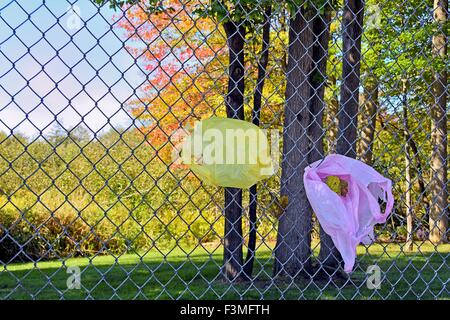 Pink and yellow plastic shopping bags caught on a chain link fence. - Stock Photo
