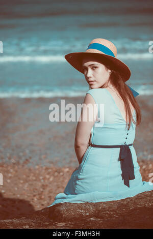 Beautiful young historical girl sitting on the beach in a blue dress and wearing a straw hat - Stock Photo