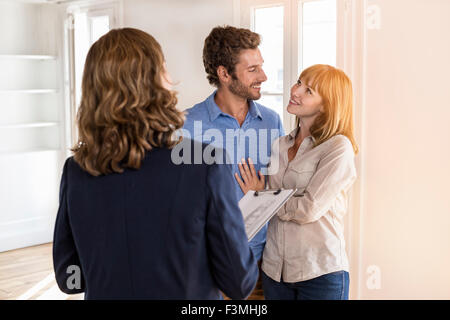 Real estate agent showing modern white apartment to future owners couple - Stock Photo