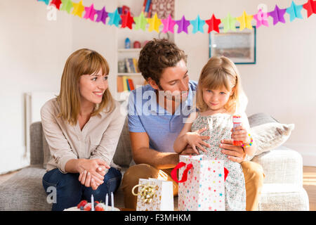 Little girl celebrating birthday party in modern house with her parents. Looking at camera - Stock Photo