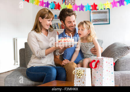 Little girl celebrating birthday party in modern house. She blows the candles - Stock Photo
