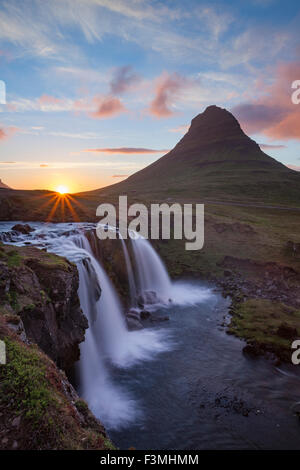 Sunset over Kirkjufell mountain and waterfall, Grundarfjordur, Snaefellsnes Peninsula, Vesturland, Iceland. - Stock Photo