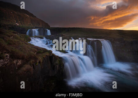 Sunset over Kirkjufell waterfall, Grundarfjordur, Snaefellsnes Peninsula, Vesturland, Iceland. - Stock Photo
