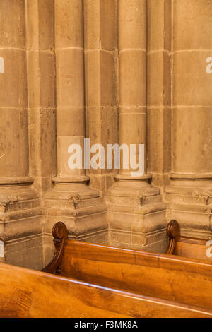 Abstract contrast between stone columns and wooden pews in Saint Peter's Cathedral, Geneva, Switzerland - Stock Photo