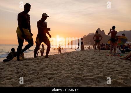 RIO DE JANEIRO, BRAZIL - FEBRUARY 21, 2014: Silhouettes of people walk along Ipanema Beach at sunset. - Stock Photo