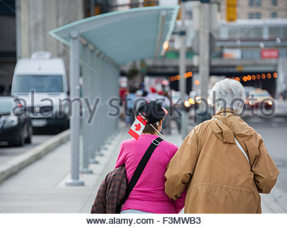 Looking after our elders: Two women walk down the sidewalk on a busy city street during Canada's Day Celebrations. - Stock Photo