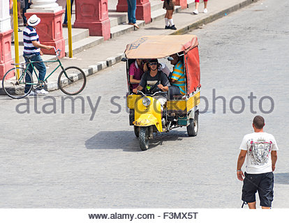 Transportation in Cuba. Yellow Auto rickshaw or moped taxi on a street in Santa Clara, Cuba, carrying passengers. - Stock Photo