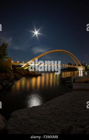 Illuminated arch bridge at night with a harvest moon.
