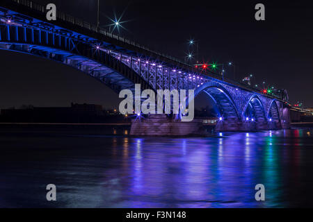 The Peach Bridge linking Canada to the US at Fort Erie, illuminated in purple. - Stock Photo