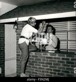 Jan. 04, 1956 - Roger Moore (Ivanhoe) and his singer wife Dorothy Squires, are making a cocktail bar in their home - Stock Photo